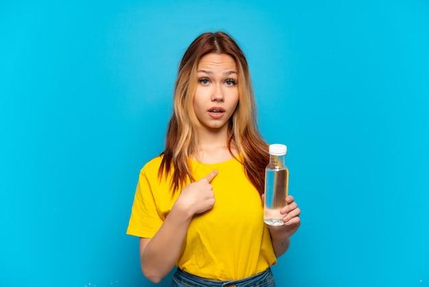 驚きの表情で孤立した青い背景の上に水のボトルを持つティーンエイジャーの女の子
