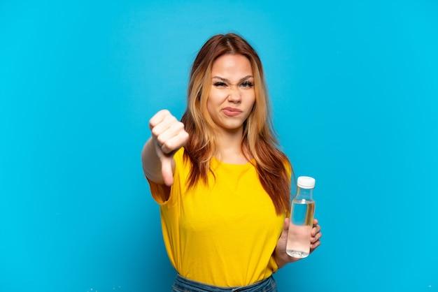 Девушка-подросток с бутылкой воды на изолированной синей поверхности показывает большой палец вниз с отрицательным выражением лица