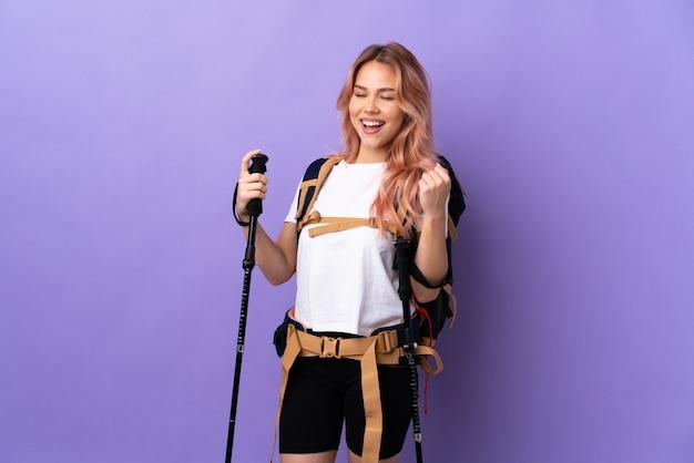 Девушка-подросток с рюкзаком и треккинговыми палками над изолированной фиолетовой стеной празднует победу