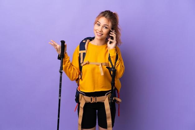 Девушка-подросток с рюкзаком и треккинговыми палками над изолированной фиолетовой стеной разговаривает с кем-то по мобильному телефону