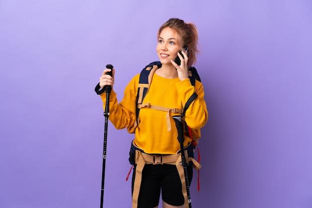 Девушка-подросток с рюкзаком и треккинговыми палками над изолированной фиолетовой стеной разговаривает по мобильному телефону