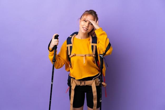 Девушка-подросток с рюкзаком и треккинговыми палками над изолированной фиолетовой стеной смотрит вдаль рукой, чтобы что-то посмотреть