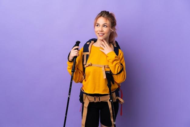 Девушка-подросток с рюкзаком и треккинговыми палками над изолированной фиолетовой стеной смотрит вверх, улыбаясь
