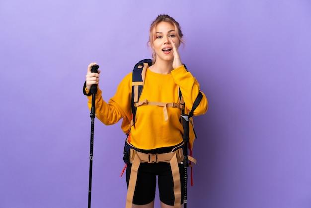 Девушка-подросток с рюкзаком и треккинговыми палками над изолированной фиолетовой стеной кричит с широко открытым ртом