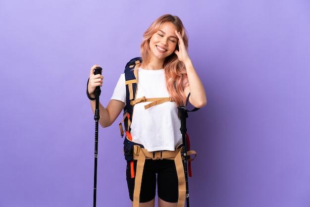 Девушка-подросток с рюкзаком и треккинговыми палками над изолированной фиолетовой стеной много улыбается