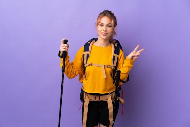 Девушка-подросток с рюкзаком и треккинговыми палками над изолированной фиолетовой стеной улыбается и показывает знак победы