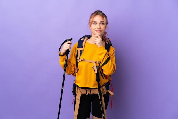 Девушка-подросток с рюкзаком и треккинговыми палками над изолированной фиолетовой стеной думает об идее, глядя вверх