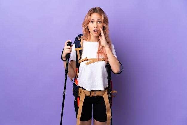 Девушка-подросток с рюкзаком и треккинговыми палками над изолированной фиолетовой стеной с удивлением и шокированным выражением лица