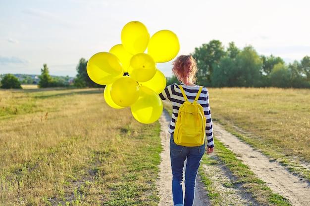 バックパックと黄色い風船が田舎道を走っているティーンエイジャーの女の子、背面図。前方に歩いて幸せな女の子、雲の空、牧草地、自然の背景