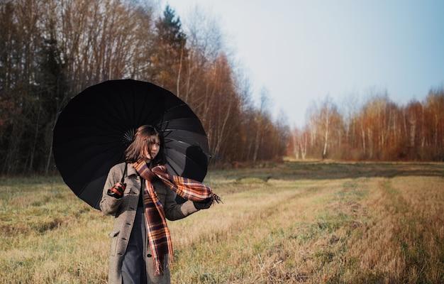秋のフィールドで黒い傘を持つティーンエイジャーの女の子