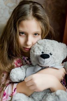 テディを保持しているピンクのドレスを着た金髪の長い髪のティーンエイジャーの女の子