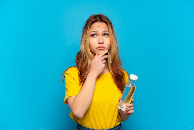 Teenager girl with a bottle of water over isolated blue background having doubts