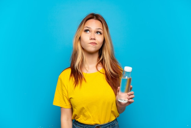 Teenager girl with a bottle of water over isolated blue background and looking up