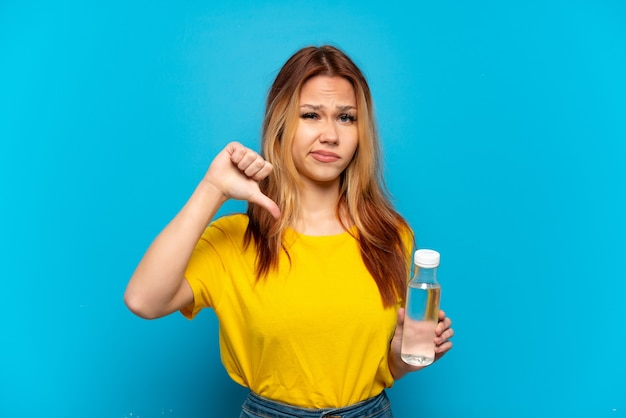 Teenager girl with a bottle of water over isolated blue background showing thumb down with negative expression