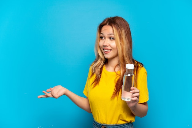 Teenager girl with a bottle of water over isolated blue background with surprise expression while looking side
