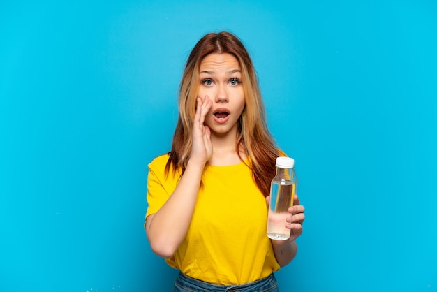 Teenager girl with a bottle of water over isolated blue background with surprise and shocked facial expression