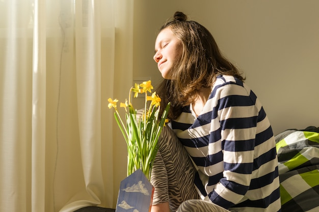 Teenager girl with bouquet of yellow spring flowers