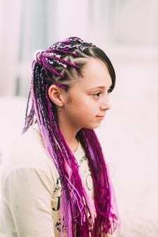 Teenager girl with bright, colorful afro braids zizi