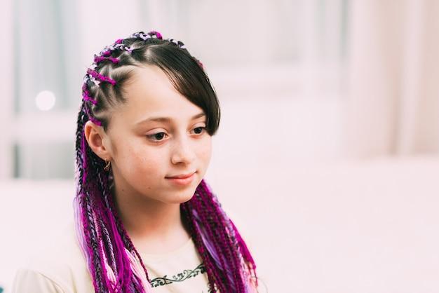 明るくカラフルなアフロブレードziziを持つティーンエイジャーの女の子