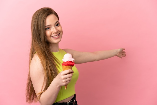Teenager girl with a cornet ice cream over isolated pink background extending hands to the side for inviting to come