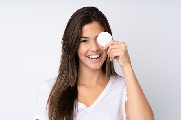 Teenager girl with cotton pad for removing makeup from her face and smiling
