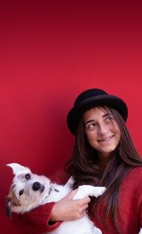 빨간색 배경에 귀여운 강아지와 함께 십 대 소녀 세로 사진 크리스마스 분위기 복사 공간