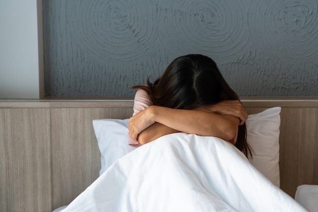 Teenager girl with depression sitting alone on bed.  sad, unhappy, disappointed concept