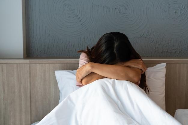 우울증에 혼자 침대에 앉아 십 대 소녀입니다. 슬프고, 불행하고, 실망한 개념