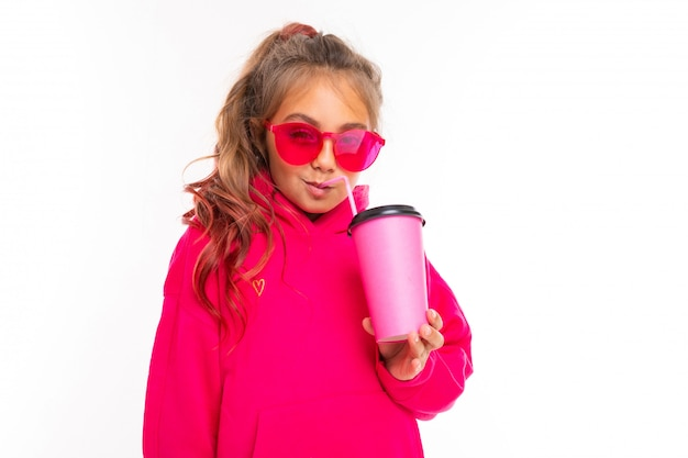Teenager girl with a glass of drink in pink glasses and a sweater on an isolated white with copy space