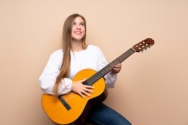 Teenager girl with guitar looking up while smiling