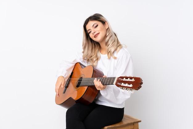 Девушка подростка с гитарой над изолированной белой предпосылкой усмехаясь много