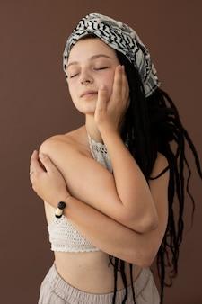 ヒッピーの服とドレッドヘアを持つティーンエイジャーの女の子