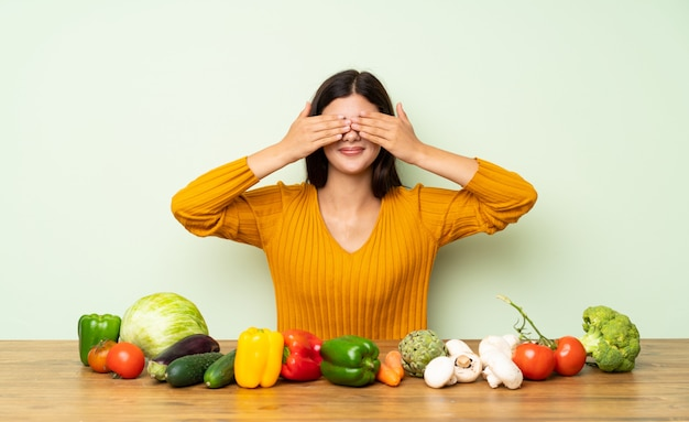 Teenager girl with many vegetables covering eyes by hands