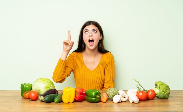 Teenager girl with many vegetables intending to realizes the solution while lifting a finger up