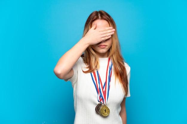 手で目を覆っている孤立した背景にメダルを持つティーンエイジャーの女の子。何かを見たくない