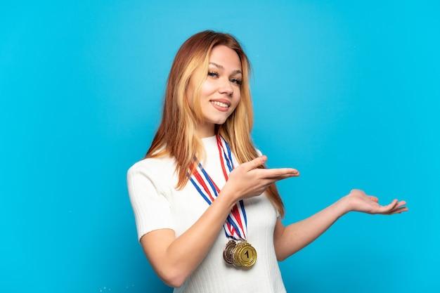孤立した背景の上にメダルを持ったティーンエイジャーの女の子が来て招待するために手を横に伸ばします