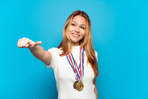 고립 된 배경 위에 메달을 가진 10 대 소녀 엄지손가락 제스처를 제공 프리미엄 사진