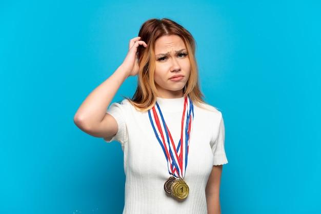 Девушка-подросток с медалями на изолированном фоне, сомневаясь