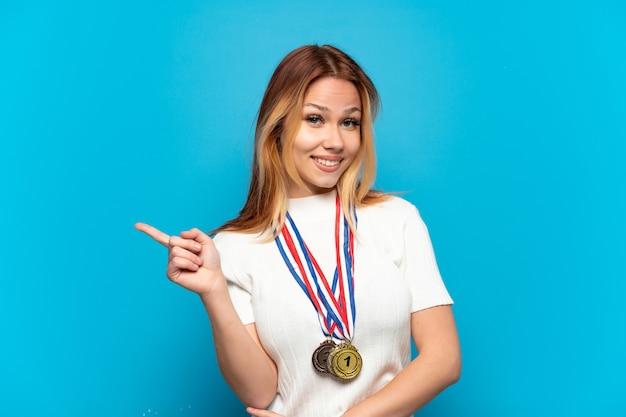 격리된 배경 위에 메달을 든 10대 소녀가 손가락을 옆으로 가리키고 있습니다.