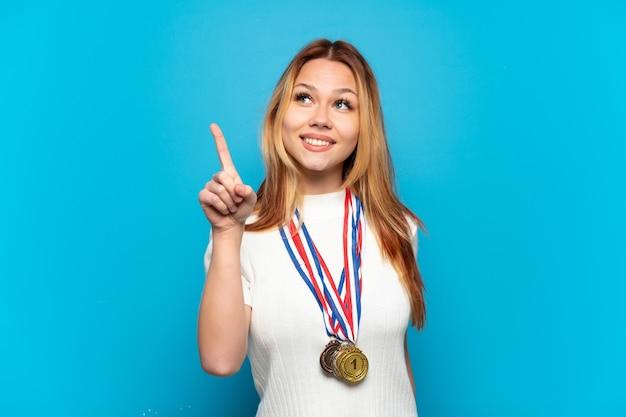 素晴らしいアイデアを指している孤立した背景にメダルを持つティーンエイジャーの女の子