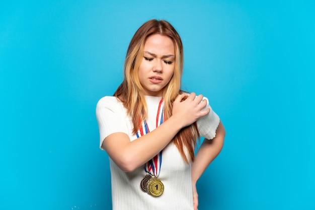 노력한 것에 대한 어깨 통증으로 고통받는 고립 된 배경 위에 메달을 가진 10 대 소녀