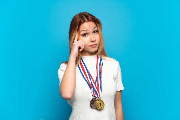 아이디어를 생각하는 고립된 배경 위에 메달을 가진 10대 소녀