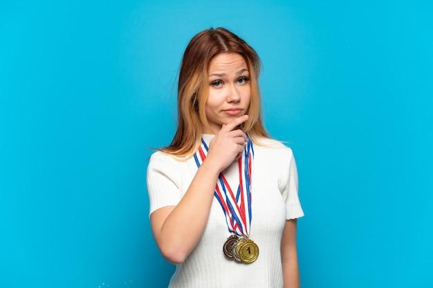 Девушка-подросток с медалями на изолированном фоне мышления Premium Фотографии