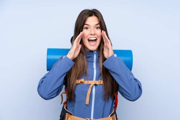 Teenager girl with a mountaineering backpack over blue wall