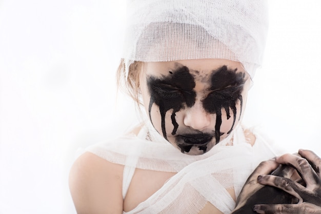 Teenager girl with mummy bandages on halloween on white isolated