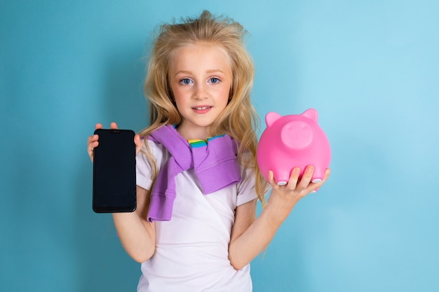 Девушка-подросток с копилкой и телефоном с макетом на синем фоне.