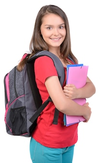Teenager girl with school backpack holding colored folders.