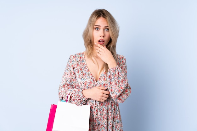 Teenager girl with shopping bag isolated on blue surprised and shocked while looking right