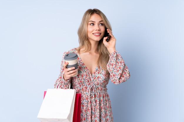 Девушка подростка с хозяйственной сумкой изолированная на голубой стене держа кофе для того чтобы отнять и мобильный телефон