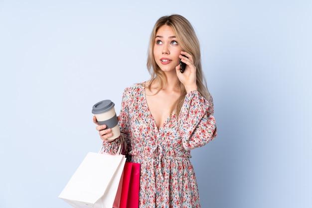 Девушка подростка с хозяйственной сумкой на голубой стене держа кофе для того чтобы отнять и чернь